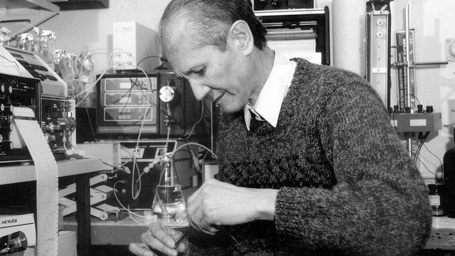 ein schwarz-weiss Foto eines Mannes, der am Mikroskop hantiert
