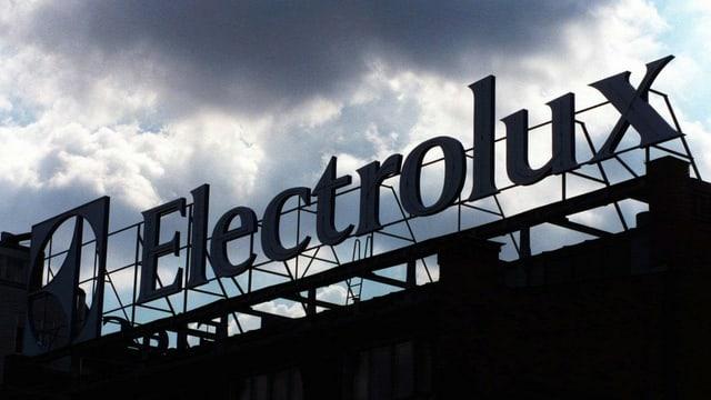 Electrolux-Schriftzug auf einem Fabrikgebäude, dunkle Wolken ziehen vorüber.