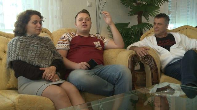 Eine Jugendlicher sitzt mit seinen Eltern auf dem Sofa.
