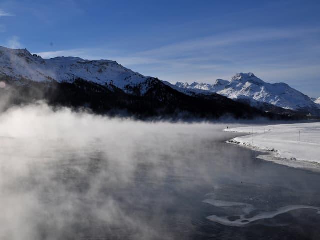 See, der raucht. Nebelschwaden hängen über dem Wasser. Sonst scheint die Sonne in der winterlichen Landschaft.