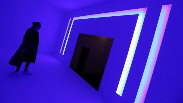 Eine Frau schaut sich eine pinke Lichtinstallation von James Turrell an.