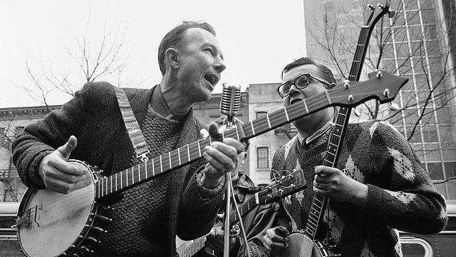 Schwarzweiss-Foto: Seeger singt mit Banjo.