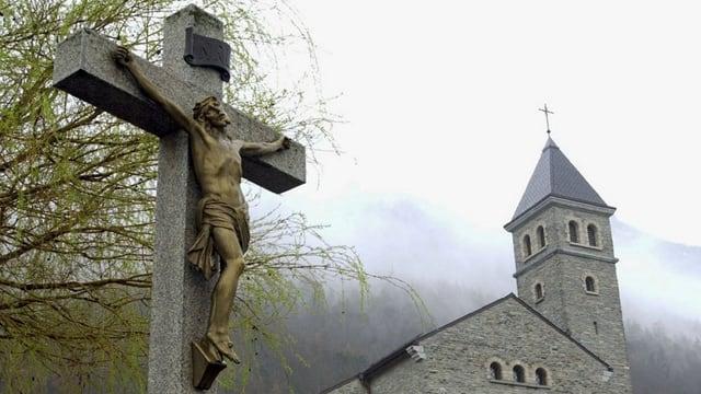 Jesus-Figur am Kreuz vor einer Kirche.