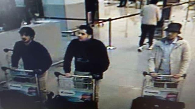Drei Männer mit Gepäck auf dem Bild einer Überwachungskamera