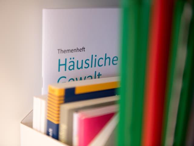 Im Bücherregal steht eine Broschüre über häusliche Gewalt.