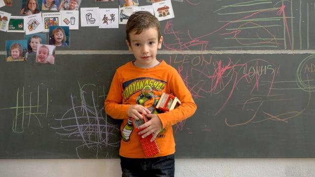 Ein Junge vor der Wandtafel.