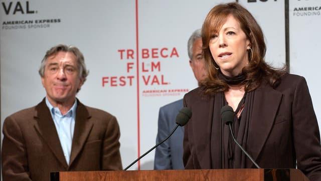 CEO Jane Rosenthal spricht anlässlich des Tribeca Film Festival; Robert De Niro hört im Hintergrund zu.