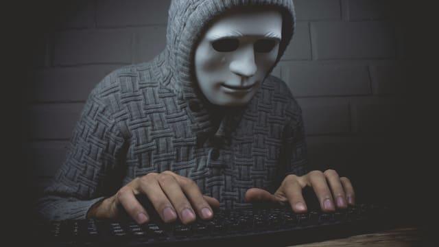 Maskierte Person an einer Tastatur.