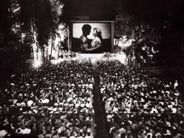 Unzählige Leute sitzen in einem Park auf Stühlen und blicken auf eine Leinwand, auf der sich ein Mann und eine Frau umarmen.
