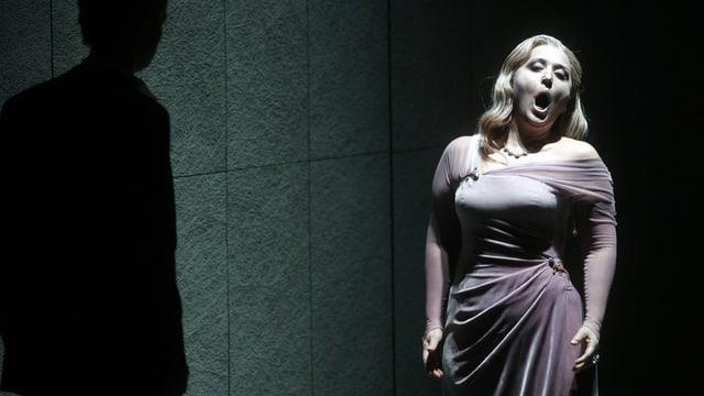 Eine Frau in einem eleganten Kleid formt mit dem Mund ein O – sie singt lauthals.