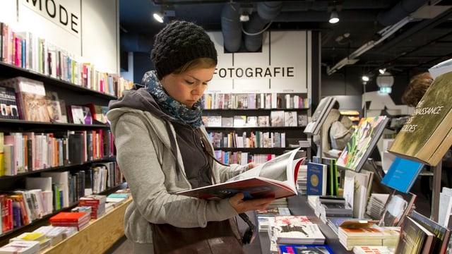Eine Frau liest in einer Buchhandlung ein Heft.