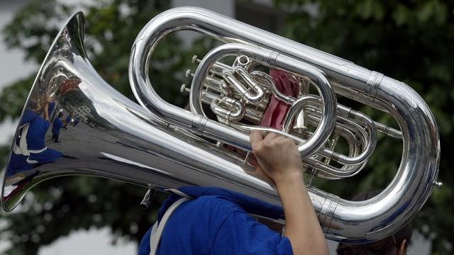 Purtret d'ina tuba che vegn purtada d'in musicist.