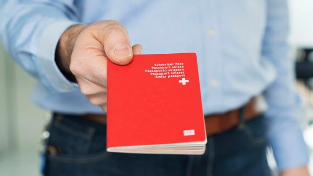 Ein Mann hält einen Schweizer Pass.