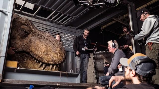 Filmset, vielen Menschen stehen um einen riesigen künstlichen Dinosaurier-Kopf