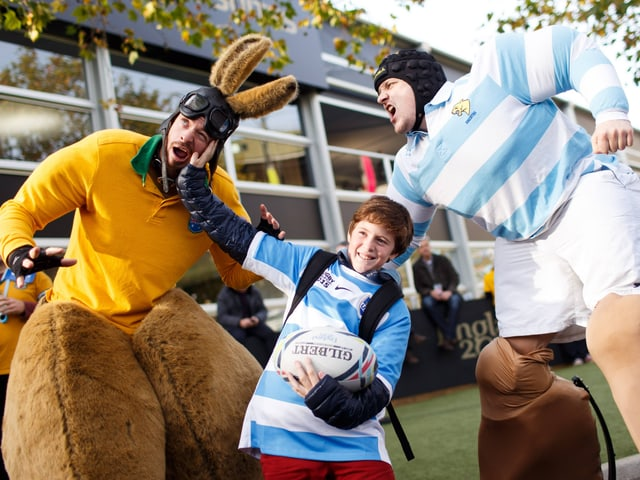Zwei verkleidete Fans von Australien und Argentinien sowie ein Kind mit Argentinien-Shirt posieren vor der Partie.