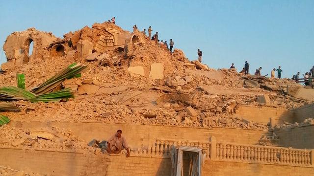 Menschen untersuchen Trümmer einer Mosche auf einem Hügel