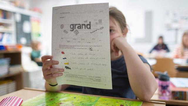 Ein Mädchen in einem Klassenzimmer studiert ein A4-Blatt während des Französischunterrichts.