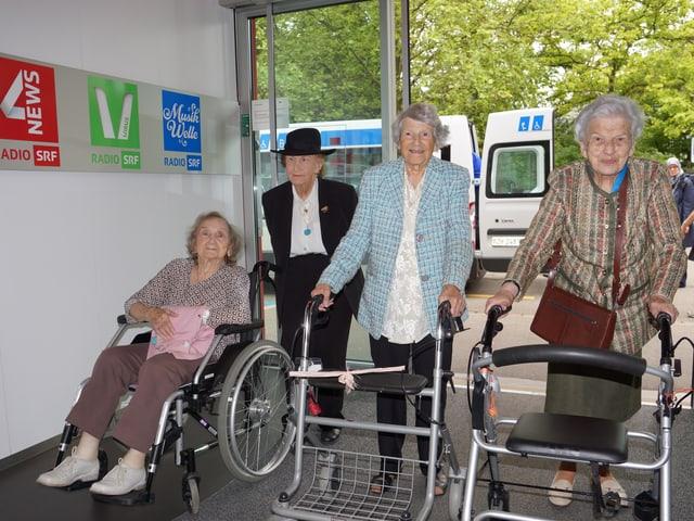 vier Damen mit Rollatoren, Gehstöcken und im Rollstuhl.