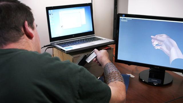 Mann mit einer seltsamen Manschette am Arm sitzt vor einem Laptop und einem Monitor, auf dem eine Hand dargestellt ist, und zieht eine Kreditkarte durch ein Lesegerät.