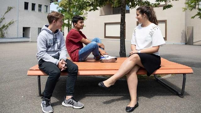 Liora Abergel sitzt mit zwei Jugendlichen auf einer Bank. Sie sprechen miteinander.
