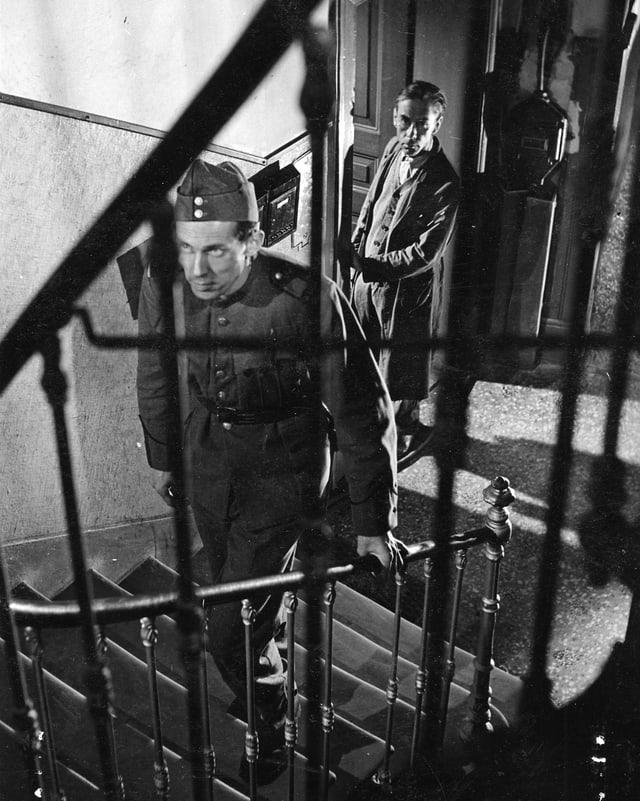 Ein Mann in Militärunform steigt eine Treppe hoch. Ein zweiter Mann beobachtet ihn dabei aus einer Tür im Hintergrund.