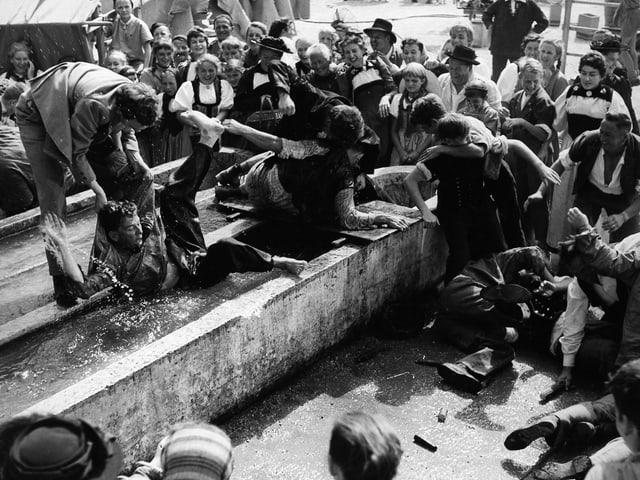 Tumult auf dem Dorfplatz. Die Dorfbewohner stehen um einen Brunnen, in welchem sich eine Handvoll Männer raufen.