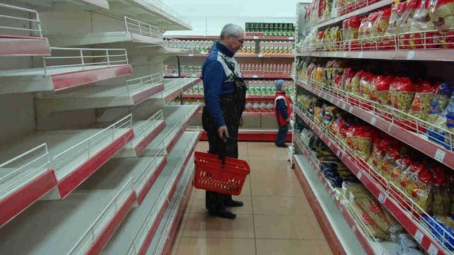 Ein Mann steht mit einem Einkaufskorb in einem Supermarkt, eine Seite des Gangs mit leeren Regalen.