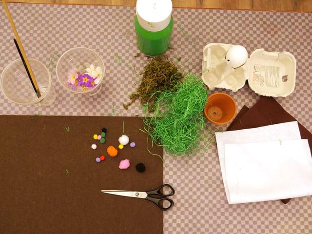 Du brauchst: Ein hartgekochtes Ei, Farbe und Pinsel, Moos oder Kunstgras, eine Schere, Blumen, einen kleinen Bommel, einen eher dickeren Filz, einen kleinen Blumentopf und zwei dünne Filze (braun und weiss).