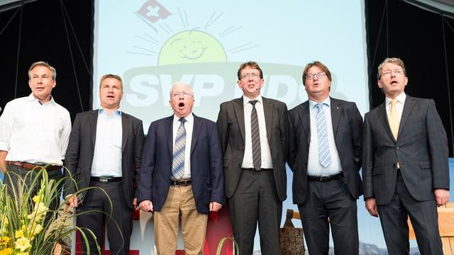 SVP-Männer rund um Präsident Toni Brunner singen auf der Bühne die Nationalhymne.