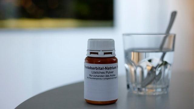 Fläschen mit Pentobarbital-Natrium auf einem Tisch, dahinter Wasserglas mit Löffel drin