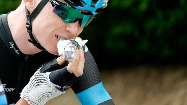 Radrennfahrer Christopher Froome beisst auf dem Rad sitzend in etwas in Alufolie.