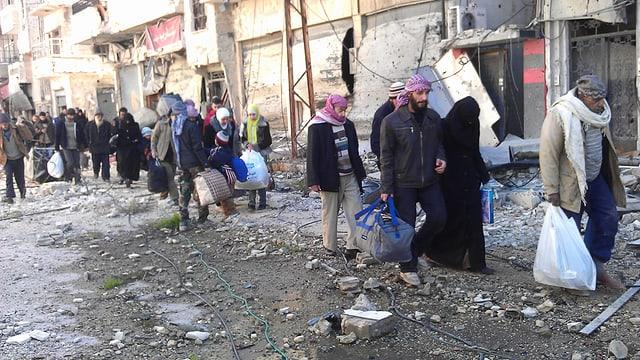 Menschen gehen mit Hab und Gut durch eine vom Krieg zerstörte Strasse.
