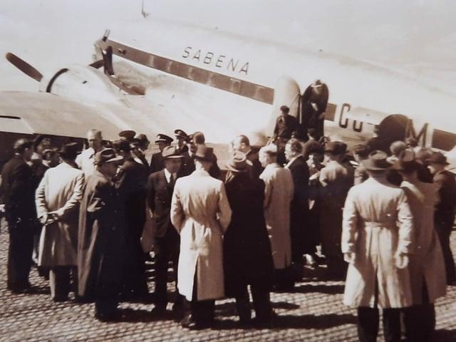 Auf einem historischen Foto warten Männer vor einem Flugzeug.