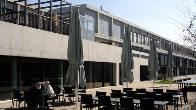 ein Betongebäude mit grossen Fenstern, davor eine Terrasse mit Tischen und Stühlen