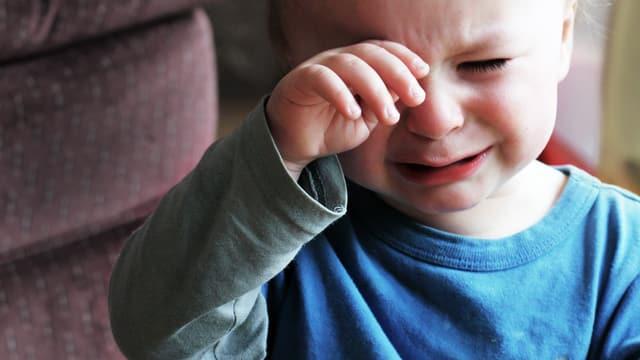Kleiner Junge weint und reibt sich die Augen