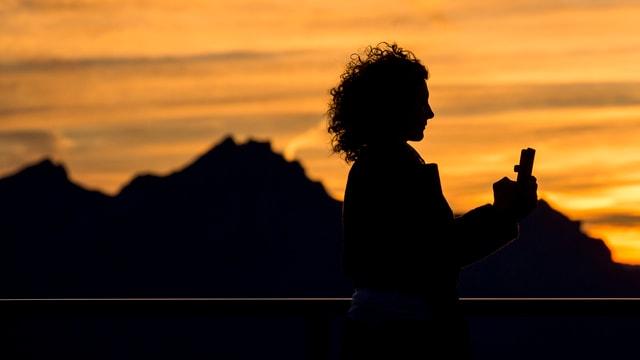 Frau macht Selfie vor Bergkulisse