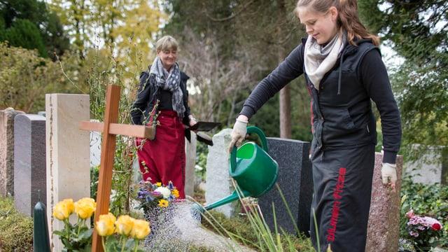 Frau giesst Blumen auf Friedhof