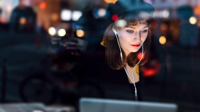 Eine Frau sitzt in einem Cafe und schaut in ihren Laptop. sie hat Kopfhörer im Ohr.