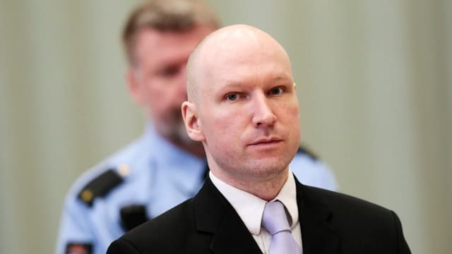 Breivik mit Anzug und Krawatte. Im Hintergrund ein Polizist.