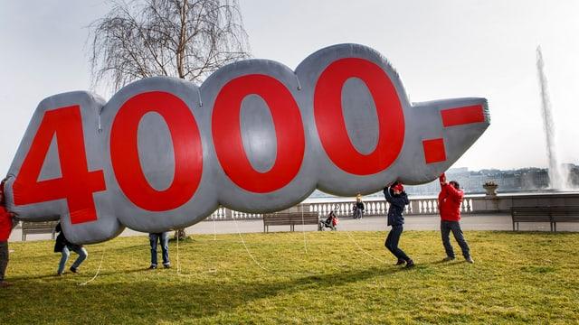Leute tragen ein Konstrukt auf dem 4000 Franken steht.