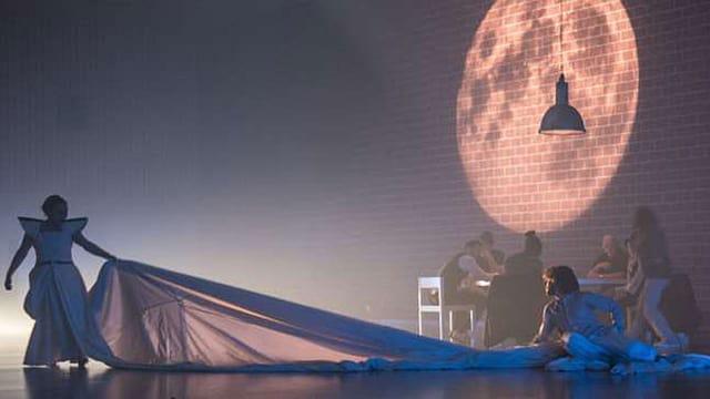 Theaterszene: Frau hält langes weisses Tuch in die Höhe