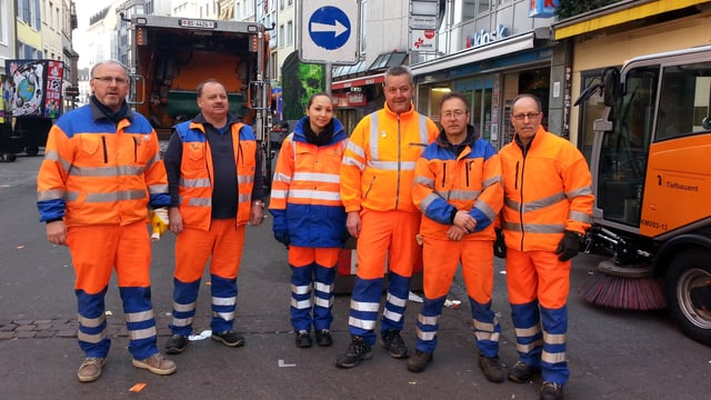 Sechs Leute in orangen Overalls