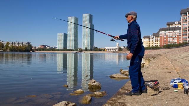 Fischer wirft Angel aus im Hintergrund die Wolkenkratzer von Astana.