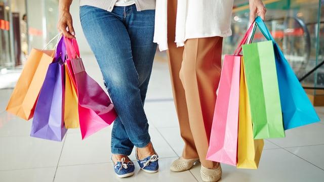 Zwei Frauen beladen mit Einkaufstaschen.