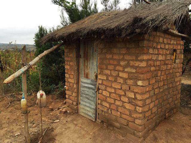 Eine Latrine in Tansania: Eine Hüte aus Bachsteinen ist zu sehen, vor der Tür hängen zwei Flaschen.