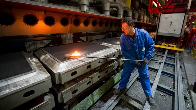 Ein Man arbeitet mit heissem Eisen.