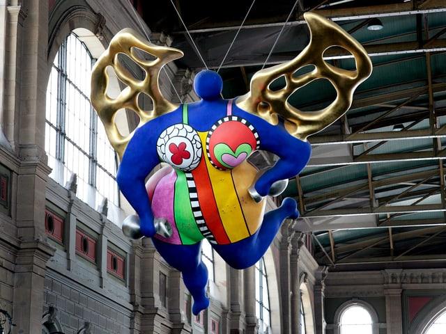 Eine farbenfrohe Figur, aufgehängt an der Decke der Bahnhofshalle in Zürich.
