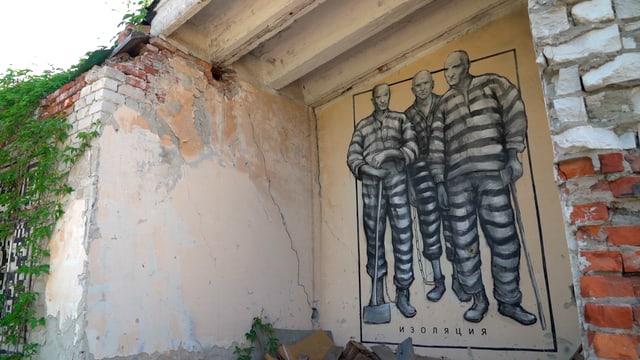 Graffiti von drei Häftlingen an einer zerfallenen Hauswand