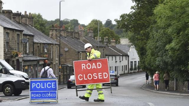 Arbeiter entfernt ein Schild von der Strasse