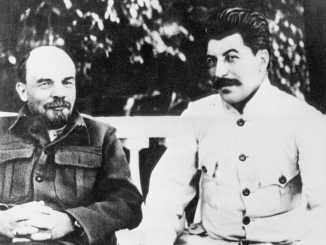 Wladimir Iljitsch Lenin sitzt neben Josef Stalin auf einer Bank